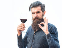 Bearded man with wine. Handsome bearded rich man with stylish hair mustache and long beard on serious face in blue fashion shirt holding glass of red wine and stock photos