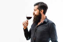 Bearded man with wine. Handsome bearded rich man with stylish hair mustache and long beard on serious face in blue fashion shirt holding glass and sniff smell of stock photos