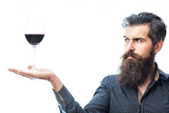 Bearded man with wine. Handsome bearded rich man with stylish hair mustache and long beard on serious face in blue fashion shirt holding glass of red wine on stock images
