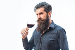 Bearded man with wine. Handsome bearded rich man with stylish hair mustache and long beard on serious face in blue fashion shirt holding glass of red wine royalty free stock photo
