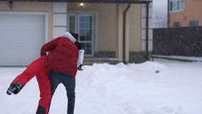 Bearded man in winter dress spinning around his girlfriend, both laughing. Happy couple have a fun in winter backyard. Bearded man in winter dress spinning stock video footage