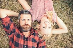 Bearded man and woman with long blond hair on summer day. Couple in love relax on green grass. Hipster and girl enjoy on. Bearded men and women with long blond royalty free stock images