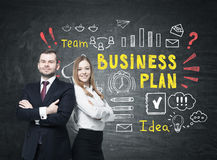 Bearded man and woman near bright business plan. Portrait of a confident bearded men and a smiling blond businesswoman standing near a blackboard with bright Royalty Free Stock Photo