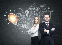 Bearded man and woman near business idea. Portrait of a confident bearded men and a smiling blond businesswoman standing near a blackboard with business idea Stock Photo