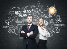 Bearded man and woman near business plan. Portrait of a confident bearded men and a smiling blond businesswoman standing near a blackboard with business plan Royalty Free Stock Image