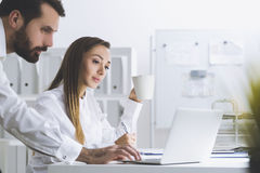 Bearded man and a woman in an office, side view Royalty Free Stock Photography