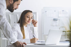 Bearded man and a woman working in office Stock Photo