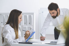 Bearded man and a woman working together Royalty Free Stock Photos