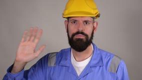 Bearded man worker in helmet saluting, waving his hand over grey background. Bearded man worker in yellow helmet saluting, waving his hand over grey background stock video footage