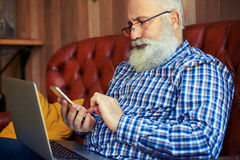 Bearded man working with gadgets at home Stock Images