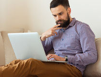 Bearded man working on laptop at home Royalty Free Stock Photography