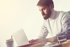 Bearded man working in office. Side view Stock Image