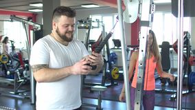 Bearded caucasian man works out in the gym with the help of the girl`s individual trainer on a crossover simulator. Bearded man works out in the gym with the stock footage