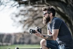 Bearded man works with vintage camera. Man with beard and mustache on concentrated face, branches on background Royalty Free Stock Images