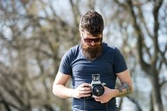 Bearded man works with vintage camera. Man with beard and mustache on concentrated face, branches on background Royalty Free Stock Photos