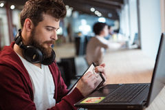 Bearded man writing on clipboard and using laptop. Bearded man with earphones on his neck writing on clipboard and using laptop Stock Image