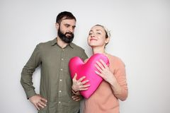 Bearded man and young girl play with red soft toy heart. Couple in love tears big heart on white background. Bearded men and young girl play with red soft toy royalty free stock image