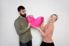 Bearded man and young girl play with red soft toy heart. Couple in love tears big heart on white background. Bearded men and young girl play with red soft toy royalty free stock photos