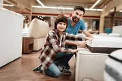 Bearded man with young son is testing mattress for softness. Testing softness of mattress. Bearded men with young son is testing mattress for softness. Testing Stock Images