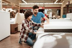 Bearded man with young son is testing mattress for softness. Testing softness of mattress. Bearded men with young son is testing mattress for softness. Testing Stock Photo