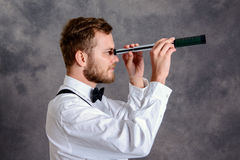 Bearded manlooking looking through a telescope Stock Images