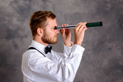 Bearded manlooking looking through a telescope Royalty Free Stock Photo