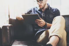 Bearded marketing specialist working digital tablet modern Interior Design Loft Office.Man relax classic sofa use. Contemporary device Hand.Blurred Background stock photo
