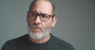 Bearded mature adult casual Businessman with glasses looking into camera