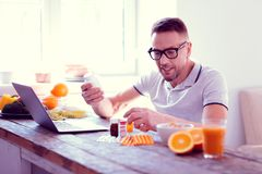 Bearded mature man feeling excited before adding supplements into his diet. Adding supplements. Bearded mature man sitting on healthy diet feeling excited before stock photo