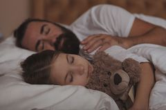 Mature bearded man resting at home with his little daughter stock image