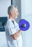 Bearded mature sportsman training with barbell in gym. Side view of bearded mature sportsman training with barbell in gym Stock Photo