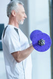 Bearded mature sportsman training with barbell in gym. Side view of bearded mature sportsman training with barbell in gym Stock Photos
