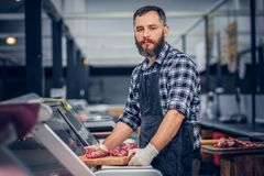 Bearded meat seller serving fresh cut meat. Bearded meat seller dressed in a fleece shirt serving fresh cut meat in a market Royalty Free Stock Image