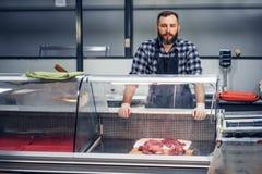 Bearded meat seller serving fresh cut meat. Bearded meat seller dressed in a fleece shirt serving fresh cut meat in a market Stock Photo