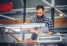 Bearded meat seller serving fresh cut meat. Bearded meat seller dressed in a fleece shirt serving fresh cut meat in a market Royalty Free Stock Images