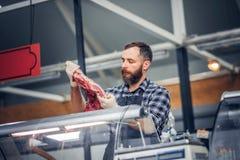 Bearded meat seller serving fresh cut meat. Bearded meat seller dressed in a fleece shirt serving fresh cut meat in a market Royalty Free Stock Photography