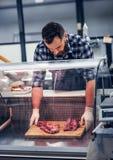 Bearded meat seller serving fresh cut meat. Bearded meat seller dressed in a fleece shirt serving fresh cut meat in a market Stock Image