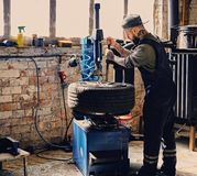 Bearded mechanic changing car`s tire on a tire. Bearded mechanic changing car`s tire on a tire changing machine in a workshop Royalty Free Stock Images