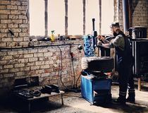 Bearded mechanic changing car`s tire on a tire. Bearded mechanic changing car`s tire on a tire changing machine in a workshop Stock Photos