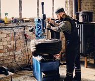Bearded mechanic changing car`s tire on a tire. Bearded mechanic changing car`s tire on a tire changing machine in a workshop Stock Images