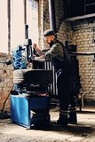 Bearded mechanic changing car`s tire on a tire. Bearded mechanic changing car`s tire on a tire changing machine in a workshop Royalty Free Stock Image