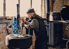 Bearded mechanic changing car`s tire on a tire. Bearded mechanic changing car`s tire on a tire changing machine in a workshop Royalty Free Stock Photo