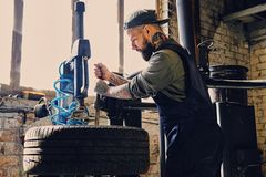 Bearded mechanic changing car`s tire on a tire. Bearded mechanic changing car`s tire on a tire changing machine in a workshop Royalty Free Stock Photos