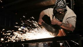 Bearded mechanic cuts metal with an angle grinder in a service station.  stock video footage