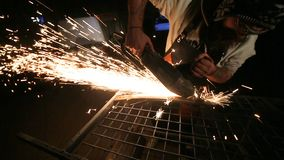 Bearded mechanic cuts metal with an angle grinder in a service station.  stock footage