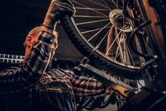 Mechanic doing bicycle wheel service manual in a workshop. stock photos