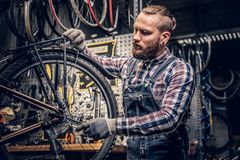 Mechanic doing bicycle wheel service manual in a workshop. stock image