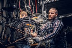 Mechanic doing bicycle wheel service manual in a workshop. royalty free stock images