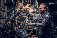 Mechanic doing bicycle wheel service manual in a workshop. Bearded mechanic doing bicycle wheel service manual in a workshop stock images