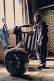 Bearded mechanic with unpacked car`s tire. Bearded mechanic with unpacked car`s tire near the tire changer machine in a workshop Stock Photos